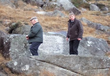 Remembering a fallen comrade ... memorial stone at Glendasan in honour of James Mernagh who died on 22 January 1957 in the Fox Rock Tunnel. Pictured are Robert Carter and Pat Casey | Joan Kavanagh