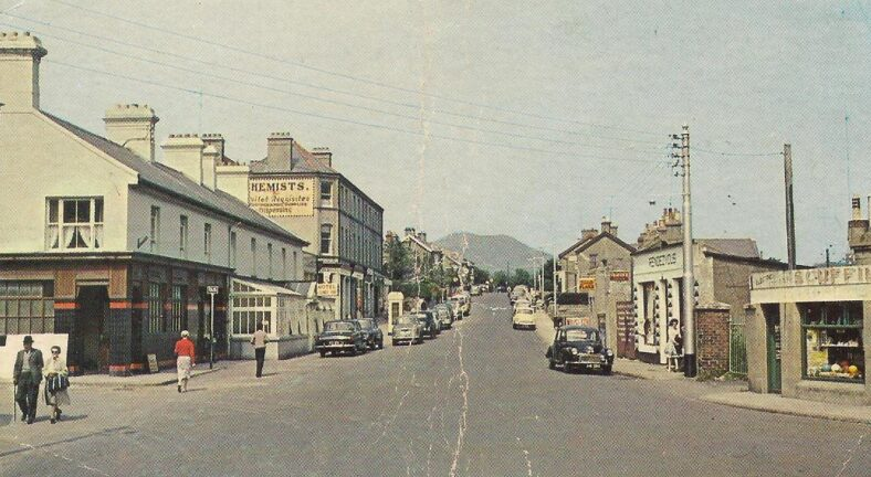 Growing population - cars vying for parking spaces on Mill Road, majestic Small Sugarloaf perfectly aligned   Old postcard.