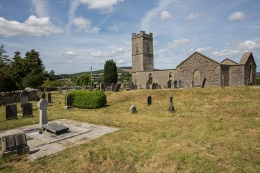 The roofless Church of Ireland with the grave of Erskine Childers in the foreground