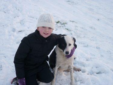 Boy and dog enjoying the snow | The Askanagap Community Development Association