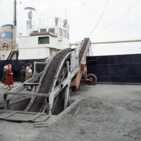 Copper ore being moved onto ship for transport