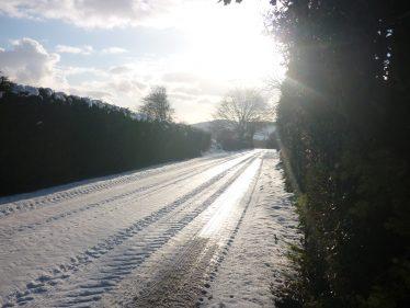 Low Winter sunlight on snowy road | The Askanagap Community Development Association